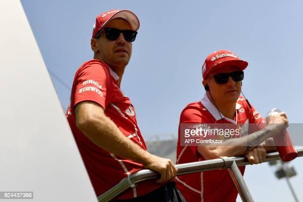 Ferrari's German driver Sebastian Vettel and Ferrari's Finnish driver Kimi Raikkonen are pictured near at the Hungaroring racing circuit in Budapest...