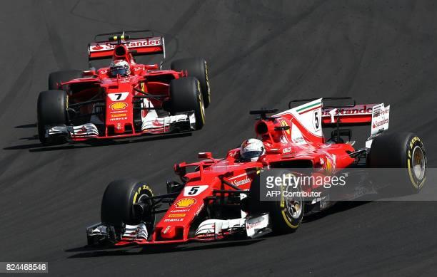 Ferrari's German driver Sebastian Vettel and Ferrari's Finnish driver Kimi Raikkonen race at the Hungaroring circuit in Budapest on July 30 during...