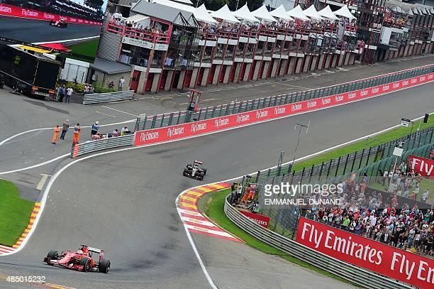 Ferrari's German driver Sebastian Vettel and Lotus F1 Team's French driver Romain Grosjean drive at the Spa-Francorchamps circuit in Spa on August 23...