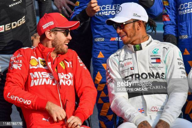 Ferrari's German driver Sebastian Vettel and Mercedes' British driver Lewis Hamilton chat as they prepare for a group picture at the Yas Marina...