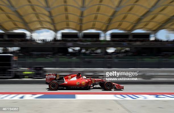 Ferrari's German driver Sebastian Vettel arrives in the pitlane during the second practice session at the Formula One Malaysian Grand Prix in Sepang...