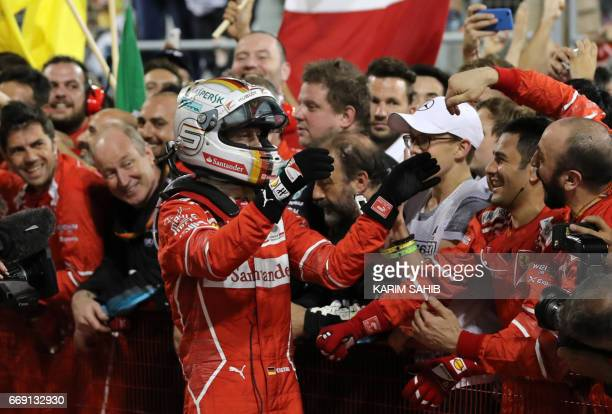 Ferrari's German driver Sebastian Vettel celebrates after winning the Bahrain Formula One Grand Prix at the Sakhir circuit in Manama on April 16 2017...