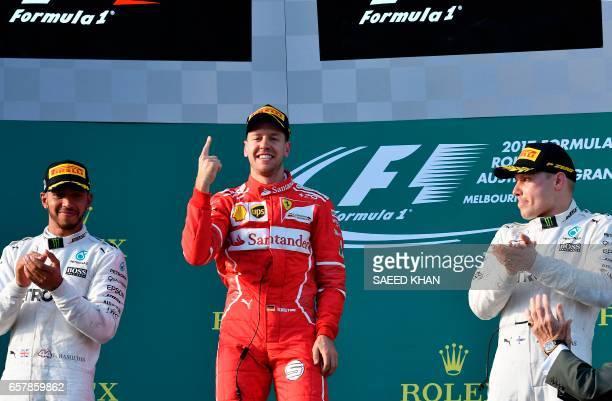 Ferrari's German driver Sebastian Vettel celebrates his victory as runnerup Mercedes' British driver Lewis Hamilton and thirdplaced Mercedes' Finnish...