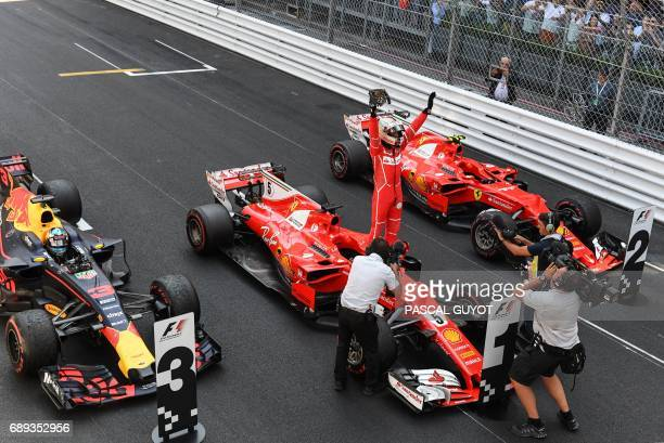 Ferrari's German driver Sebastian Vettel celebrates on his car after winning the Monaco Formula 1 Grand Prix at the Monaco street circuit on May 28...
