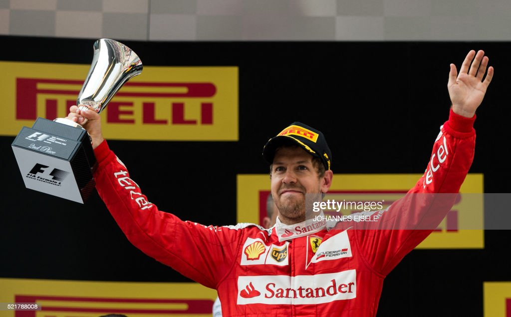 Ferrari's German driver Sebastian Vettel celebrates on podium after finishing second in the Formula One Chinese Grand Prix in Shanghai on April 17, 2016. / AFP / JOHANNES