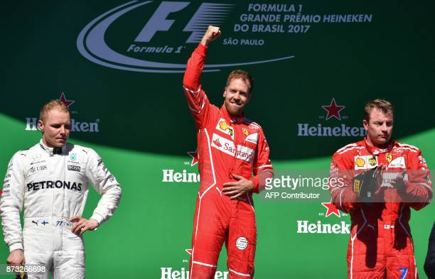 TOPSHOT Ferrari's German driver Sebastian Vettel celebrates on the podium next to runnerup Mercedes' Finnish driver Valtteri Bottas and thirdplace...
