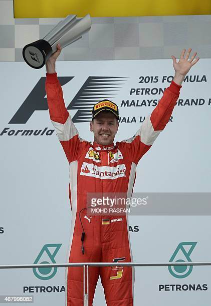 Ferrari's German driver Sebastian Vettel celebrates on the podium after winning the Formula One Malaysian Grand Prix in Sepang on March 29 2015 AFP...
