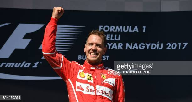 Ferrari's German driver Sebastian Vettel celebrates on the podium after winning the Formula One Hungarian Grand Prix at the Hungaroring racing...