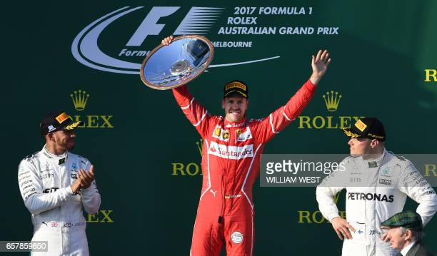 TOPSHOT Ferrari's German driver Sebastian Vettel celebrates on the podium with Mercedes' British driver Lewis Hamilton and Mercedes' Finnish driver...