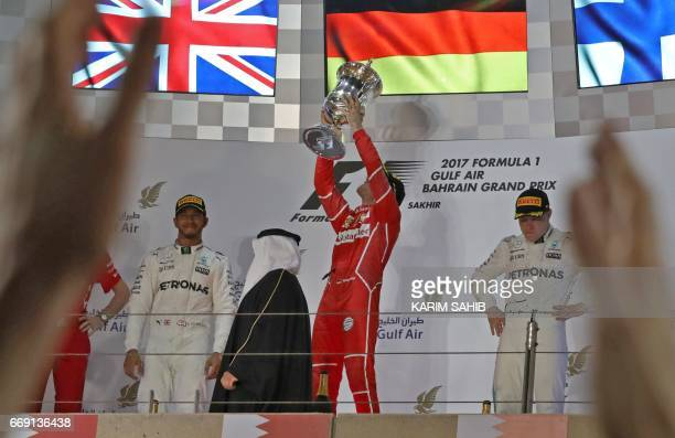 Ferrari's German driver Sebastian Vettel celebrates on the podium with Mercedes' British driver Lewis Hamilton and Mercedes' Finnish driver Valtteri...