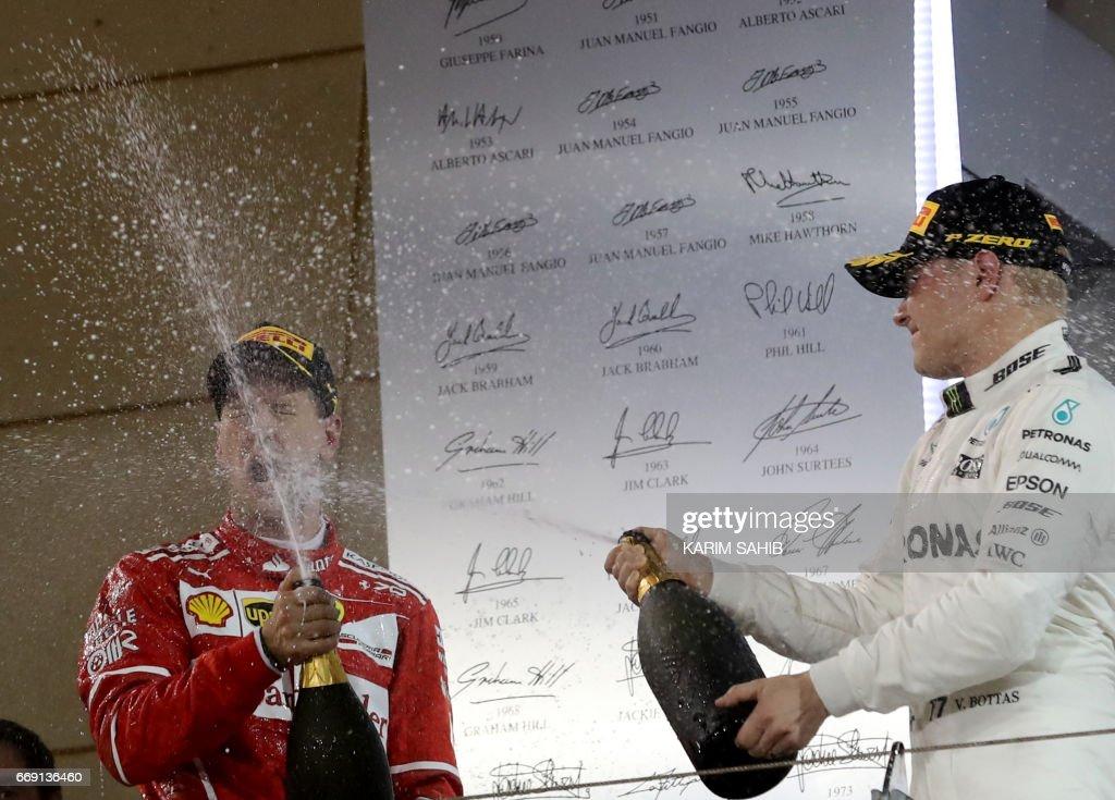 Ferrari's German driver Sebastian Vettel (L) celebrates on the podium with Mercedes' Finnish driver Valtteri Bottas after winning the Bahrain Formula One Grand Prix at the Sakhir circuit in Manama on April 16, 2017. /