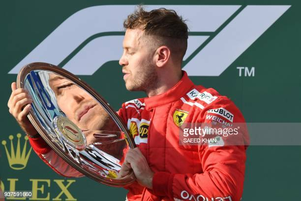 Ferrari's German driver Sebastian Vettel celebrates winning the Formula One Australian Grand Prix in Melbourne on March 25 2018 / AFP PHOTO / SAEED...