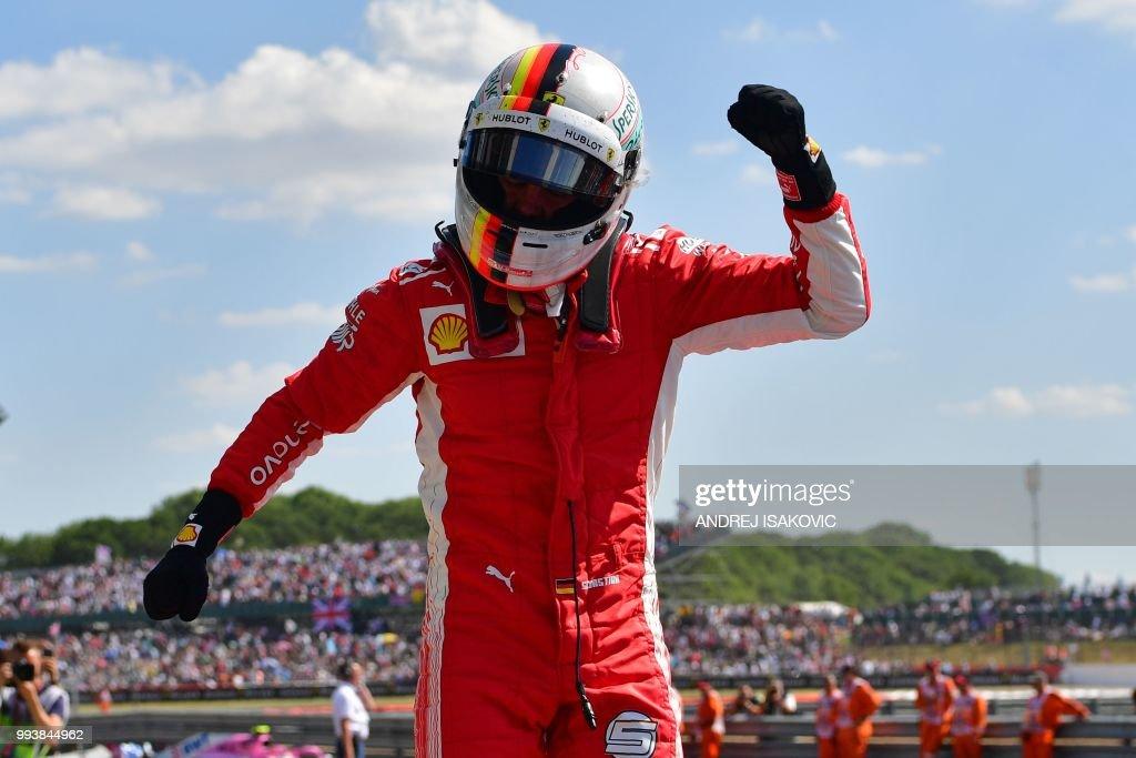 TOPSHOT - Ferrari's German driver Sebastian Vettel celebrates winning the British Formula One Grand Prix at the Silverstone motor racing circuit in Silverstone, central England, on July 8, 2018.