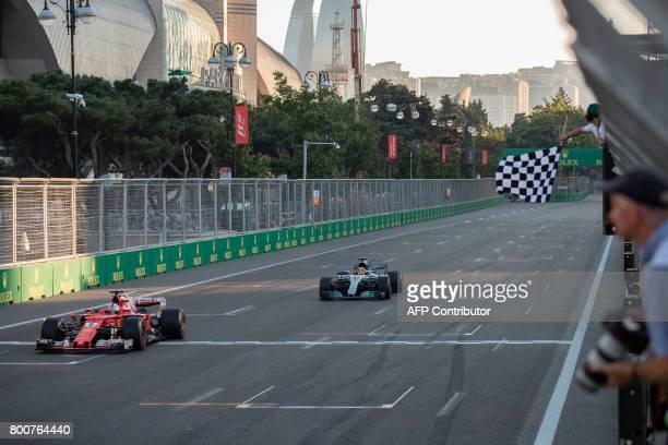 Ferrari's German driver Sebastian Vettel crosses the finish line ahead of Mercedes' British driver Lewis Hamilton during the Formula One Azerbaijan...