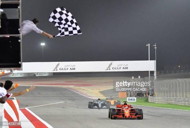 TOPSHOT Ferrari's German driver Sebastian Vettel crosses the finish line to win the Bahrain Formula One Grand Prix at the Sakhir circuit in Manama on...