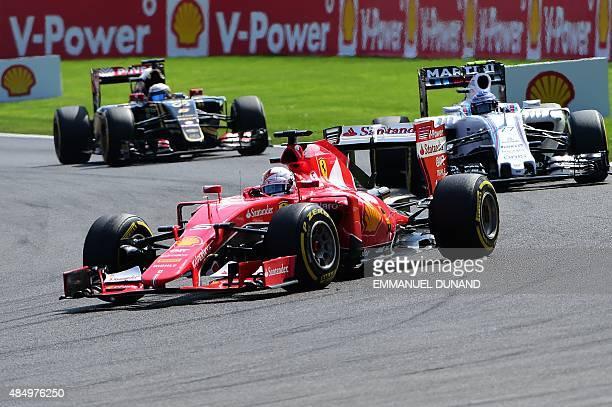 Ferrari's German driver Sebastian Vettel drives ahead of Williams Martini Racing's Finnish driver Valtteri Bottas and Lotus F1 Team's French driver...