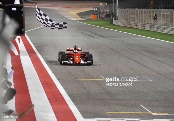Ferrari's German driver Sebastian Vettel drives his car past the chequered flag to win the Bahrain Formula One Grand Prix at the Sakhir circuit in...