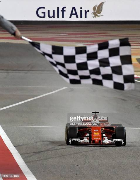Ferrari's German driver Sebastian Vettel drives his car past the chequered flag to win the Bahrain Formula One Grand Prix at the Sakhir circuit in...