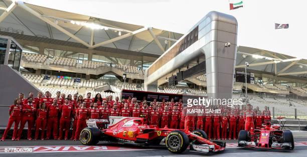 TOPSHOT Ferrari's German driver Sebastian Vettel Finnish driver Kimi Raikkonen and the Ferrari team pose for a team photo ahead of the Abu Dhabi...