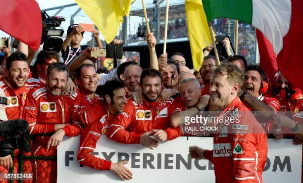 Ferrari's German driver Sebastian Vettel is congratulated by team members after his victory in the Formula One Australian Grand Prix in Melbourne on...