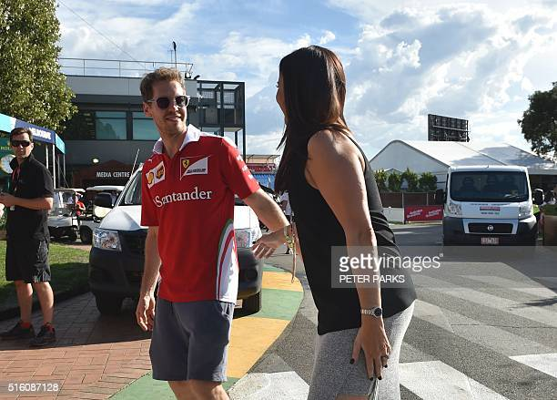 Ferrari's German driver Sebastian Vettel is grabbed by a fan ahead of the Formula One Australian Grand Prix in Melbourne on March 17 2016 / AFP /...