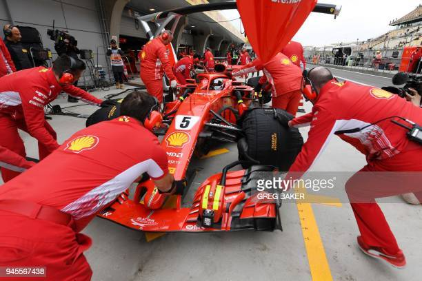 TOPSHOT Ferrari's German driver Sebastian Vettel is pushed back into the garage during practice for the Formula One Chinese Grand Prix in Shanghai on...