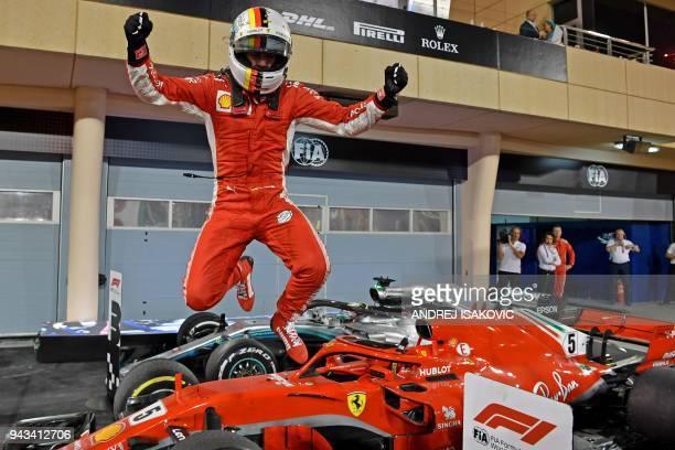 TOPSHOT Ferrari's German driver Sebastian Vettel jumps out of his car after winning the Bahrain Formula One Grand Prix at the Sakhir circuit in...