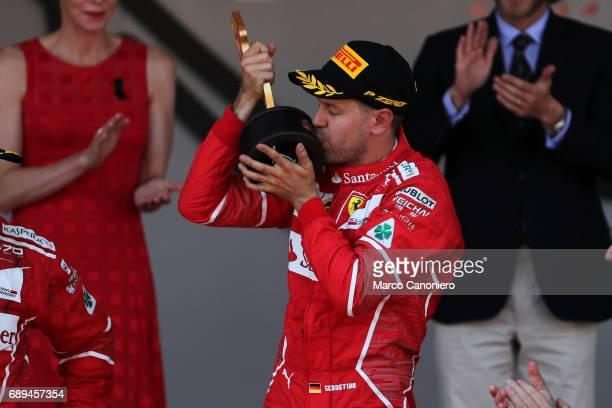 Ferrari's German driver Sebastian Vettel kiss his trophy on the podium after winning the Monaco Formula 1 Grand Prix