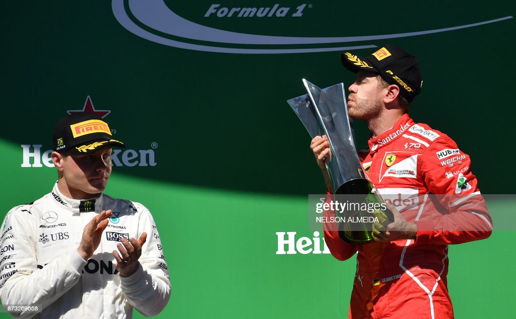 TOPSHOT - Ferrari's German driver Sebastian Vettel (R) kisses his trophy on the podium as runner-up Mercedes' Finnish driver Valtteri Bottas applauds at the end of the Brazilian Formula One Grand Prix, at the Interlagos circuit in Sao Paulo, Brazil, on November 12, 2017. / AFP PHOTO / Nelson ALMEIDA