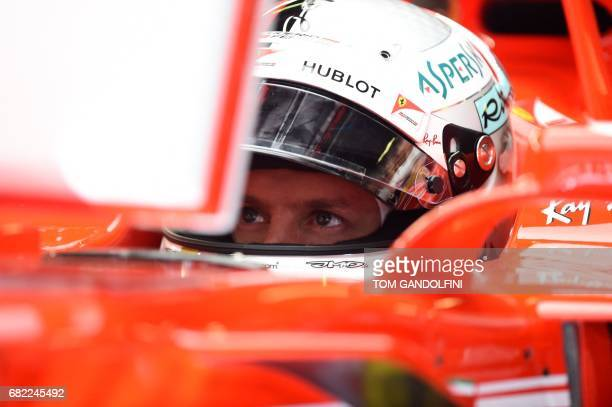 Ferrari's German driver Sebastian Vettel looks at a screen in the pits during the first practice session at the Circuit de Catalunya on May 12 2017...