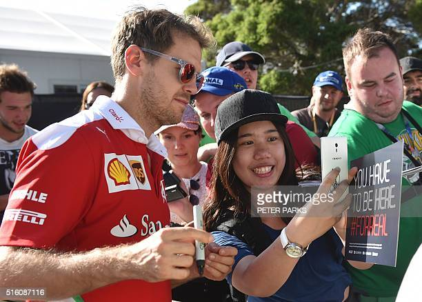 Ferrari's German driver Sebastian Vettel poses for pictures with a fan ahead of the Formula One Australian Grand Prix in Melbourne on March 17 2016 /...