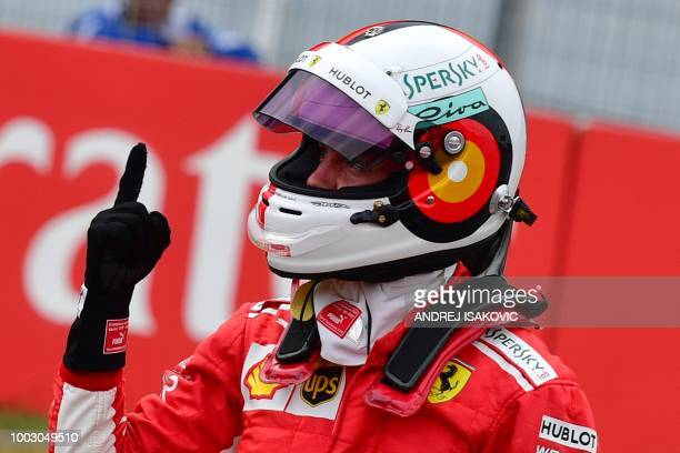 Ferrari's German driver Sebastian Vettel reacts after taking the pole position during the qualifying session on the eve of the German Formula One...