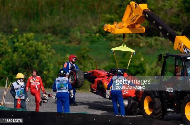 Ferrari's German driver Sebastian Vettel reacts while a crane lifts his car during the F1 Brazil Grand Prix at the Interlagos racetrack in Sao Paulo...
