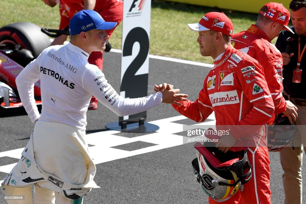 Ferrari's German driver Sebastian Vettel (R) shakes hands with Mercedes' Finnish driver Valtteri Bottas (L) during the qualifying at the Hungaroring racing circuit in Budapest on July 29, 2017 prior to the Formula One Hungarian Grand Prix. /