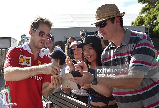 Ferrari's German driver Sebastian Vettel signs autographs for fans ahead of the Formula One Australian Grand Prix in Melbourne on March 17 2016 / AFP...