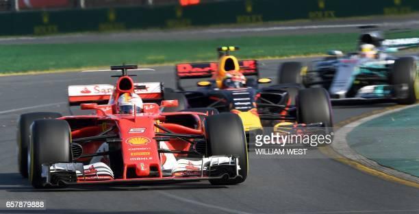 Ferrari's German driver Sebastian Vettel speeds through a corner ahead of Red Bull's Dutch driver Max Verstappen and Mercedes' British driver Lewis...