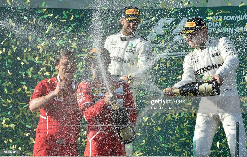 Ferrari's German driver Sebastian Vettel (2nd L) sprays champagne as he celebrates his victory with runner-up Mercedes' British driver Lewis Hamilton (C-behind), third-placed Mercedes' Finnish driver Valtteri Bottas (R) and Ferrari's trackside engineering team member Luigi Fraboni (L) on the podium at the end of the Australian Grand Prix in Melbourne on March 26, 2017. /