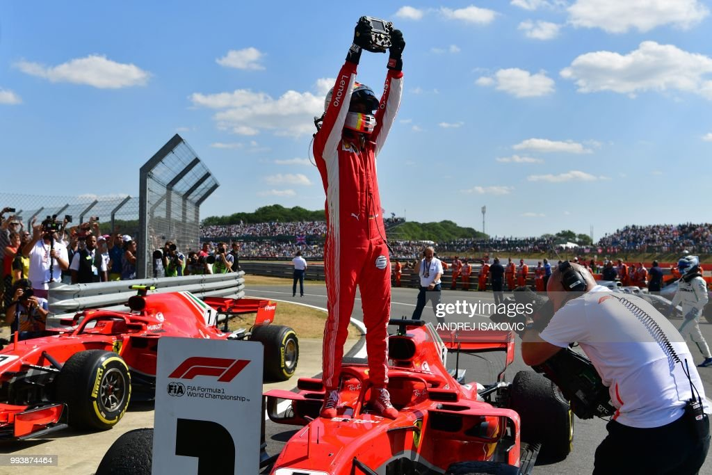 Ferrari's German driver Sebastian Vettel stands on his car as he celebrates winning the British Formula One Grand Prix at the Silverstone motor racing circuit in Silverstone, central England, on July 8, 2018.
