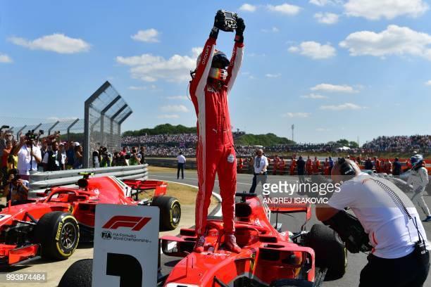Ferrari's German driver Sebastian Vettel stands on his car as he celebrates winning the British Formula One Grand Prix at the Silverstone motor...