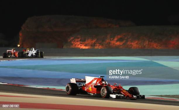 Ferrari's German driver Sebastian Vettel steers his car during the Bahrain Formula One Grand Prix at the Sakhir circuit in Manama on April 16 2017...