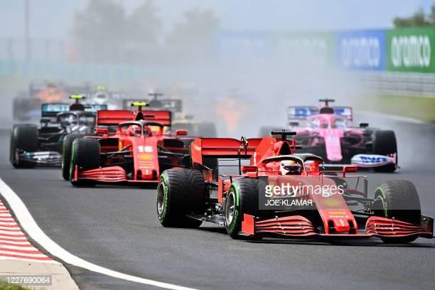 Ferrari's German driver Sebastian Vettel steers his car in front of Ferrari's Monegasque driver Charles Leclerc during the Formula One Hungarian...