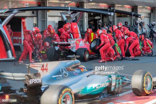 Ferrari's German driver Sebastian Vettel takes a pit stop as Mercedes' British driver Lewis Hamilton drives past during the Formula One Azerbaijan...