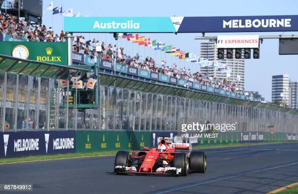 Ferrari's German driver Sebastian Vettel takes the chequered flag to win the Formula One Australian Grand Prix in Melbourne on March 26 2017 / AFP...