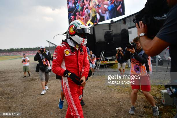 TOPSHOT Ferrari's German driver Sebastian Vettel walks to the pits after he was forced to abandon during the German Formula One Grand Prix at the...