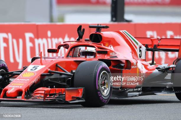 Ferrari's German driver Sebastian Vettel waves after finishing first in the qualifying session on the eve of the German Formula One Grand Prix at the...