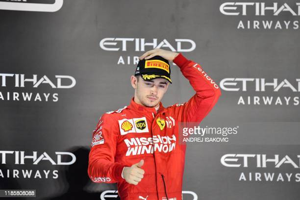 Ferrari's Monegasque driver Charles Leclerc celebrates his third place finish on the podium at the Yas Marina Circuit in Abu Dhabi after the final...