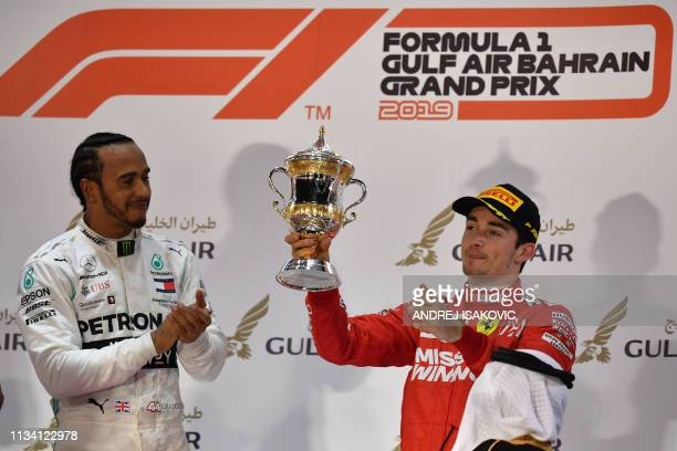 Ferrari's Monegasque driver Charles Leclerc celebrates on the podium after placing third at the Formula One Bahrain Grand Prix next to Mercedes'...
