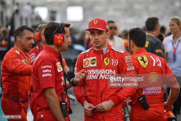 Ferrari's Monegasque driver Charles Leclerc chats with an engineer on the grid at the Yas Marina Circuit in Abu Dhabi ahead of the final race of the...