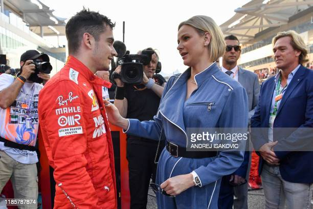 Ferrari's Monegasque driver Charles Leclerc greets Princess Charlene of Monaco at the Yas Marina Circuit in Abu Dhabi, ahead of the final race of the...