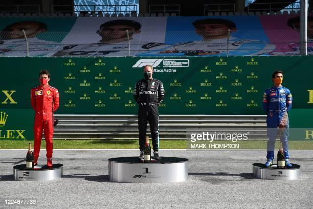 Ferrari's Monegasque driver Charles Leclerc Mercedes' Finnish driver Valtteri Bottas and McLaren's British driver Lando Norris celebrate on the...